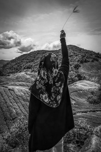 Rear view of woman wearing hijab holding plant while standing against mountains