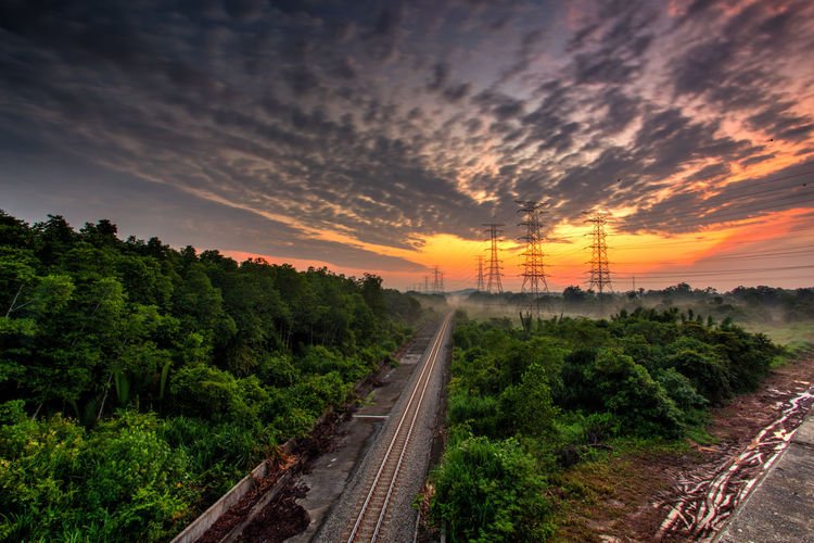Railroad against beautiful burning sky at sunrise. Industrial landscape with railroad, colorful blue sky with burning clouds, sun, trees and green grass. Railway junction. Beauty In Nature Burning Cargo Day Landscape Nature No People Outdoors People Platform Power Line  Power Lines Railroad Track Scenics Sky Sunrise Sunset Train Train Tracks Tree