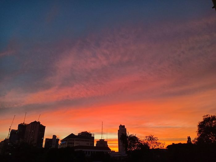 Silhouette of buildings against cloudy sky during sunset