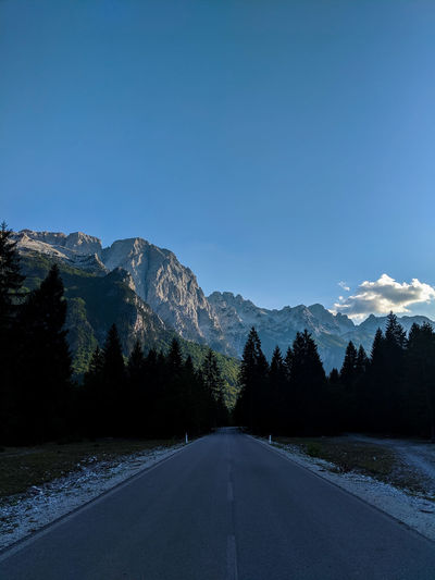 Empty road along trees and mountains against blue sky