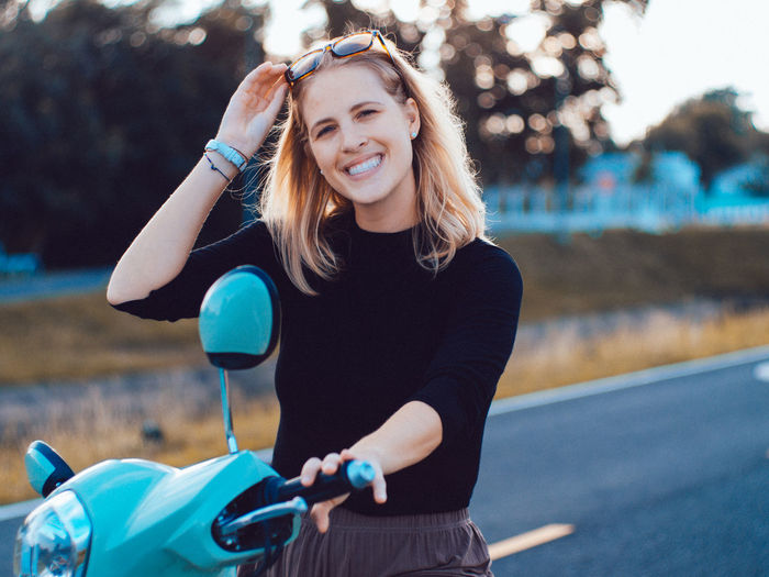 Portrait of young woman sitting on motor scooter