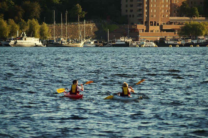 Rear view of men kayaking in river