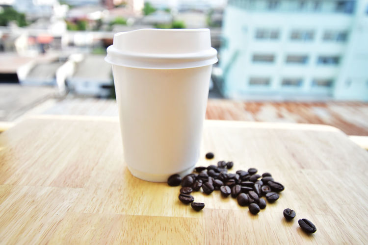 Close-Up Of Disposable Cup And Coffee Beans On Table