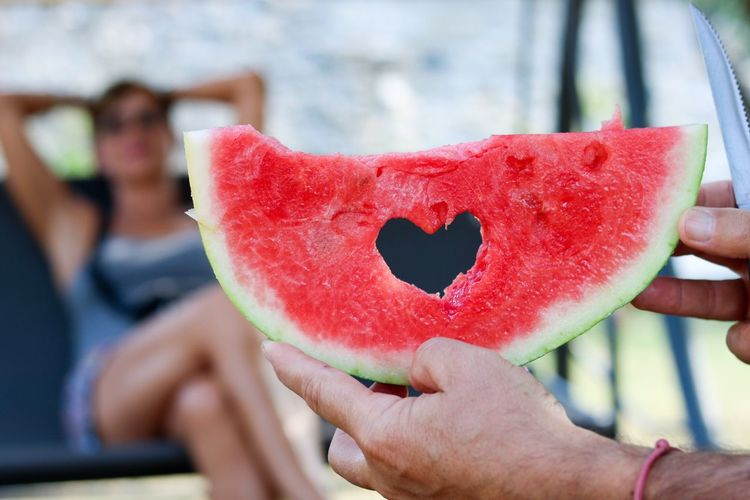Cropped hand of man holding watermelon while woman relaxing on chair in background