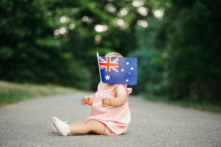 Cute girl holding australian flag sitting on road