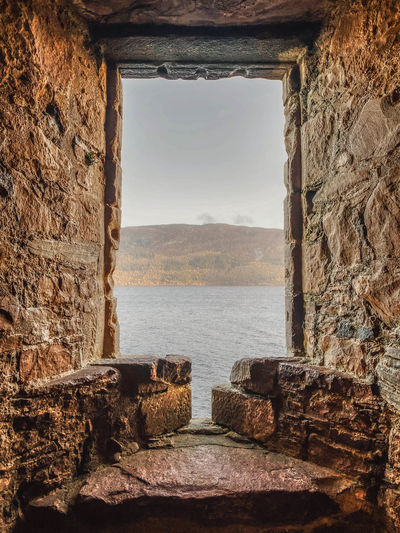 Stone wall by sea against sky seen through window