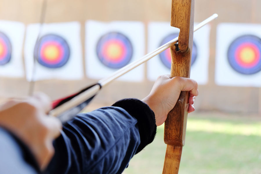Archer holds his bow aiming at a target Arrow Bow Archer Archery Archery Bows Archery Competition Archery Target Close-up Human Hand One Person People Skill  Sport Sports Photography