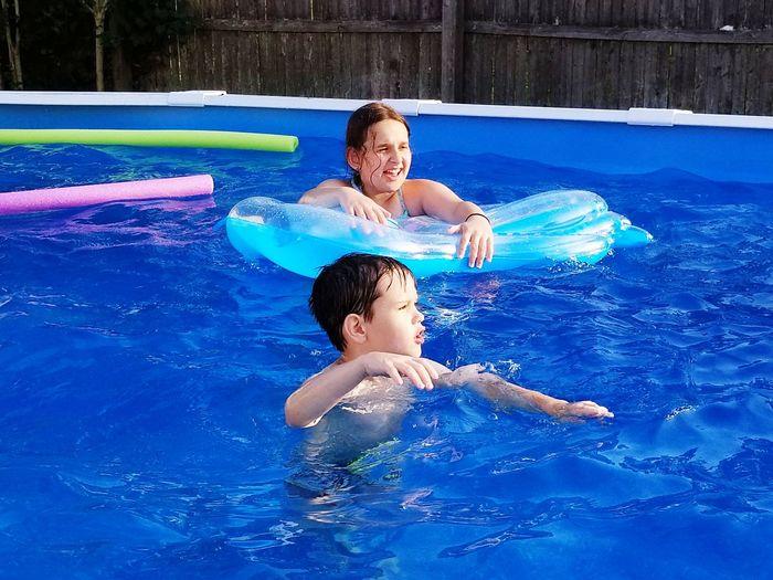 Siblings Enjoying In Wading Pool