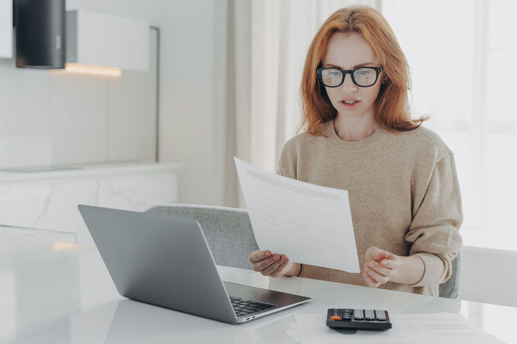 Mid adult woman using laptop on table