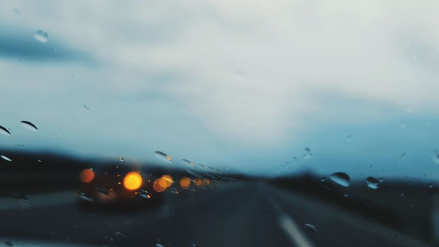 Cars on road seen through wet windshield