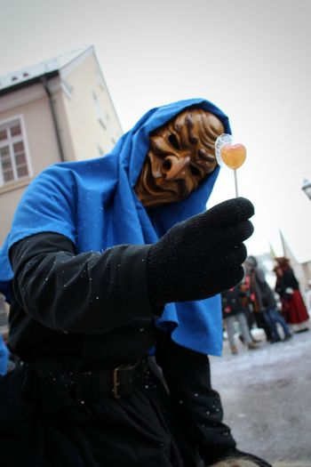 Person with mask showing candy on street
