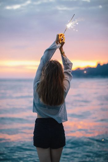 Woman with lit sparkler standing at beach during sunset