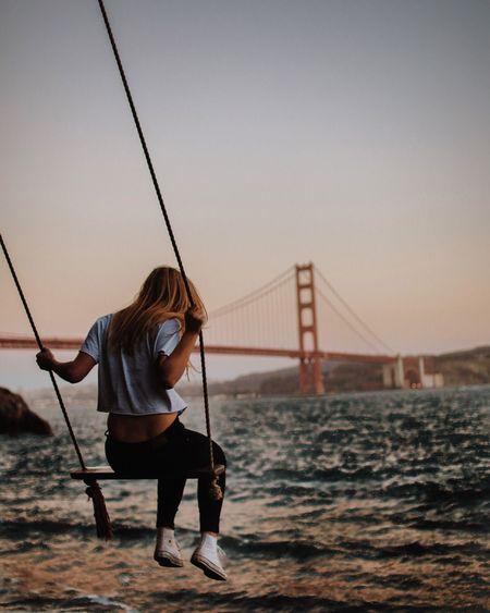 Rear view of man fishing on suspension bridge