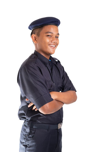 Young Asian man in police uniform isolated on white background. White Background Studio Shot Cut Out One Person Clothing Looking At Camera Standing Young Adult Cap Portrait Men Police Officer Security Face Smile Service Smiling Occupation Uniform Young Men Three Quarter Length Indoors  Happiness