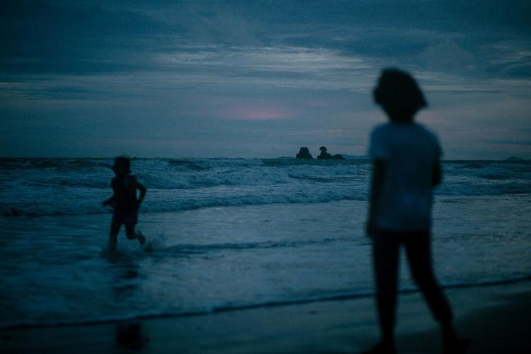 Silhouette siblings at beach against sky during dusk