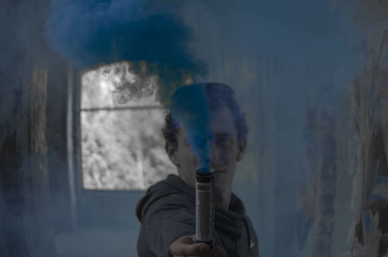 Portrait Of Man Holding Blue Distress Flare In Corridor