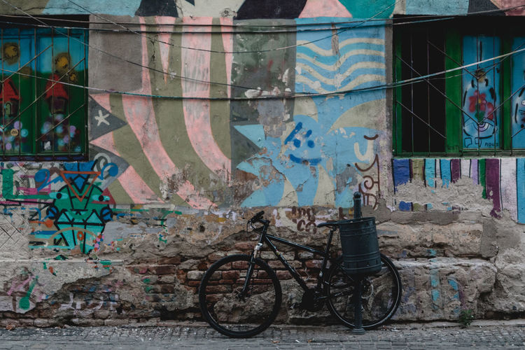 A new bicycle rests against a trash can and colorful graffiti facade in Romania. - IG: @LostBoyMemoirs - IG: @LostBoyMemoirs Streetwise Photography Steetphotography Street Photography The Week on EyeEm Best EyeEm Shot My Best Photo Graffiti Built Structure No People Abandoned Building Street Art Bicycle Building Exterior