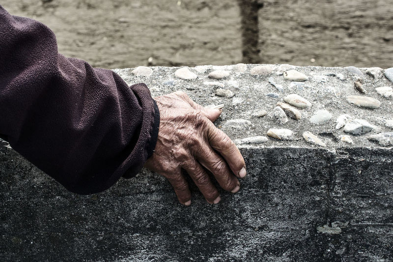 Close-up of hand leaning on textured wall