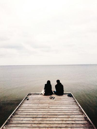 Man sitting on pier at sea