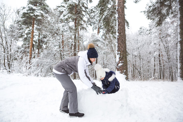 Mom and daughter play snow games, build a fortress, make snowballs. winter entertainment outside,