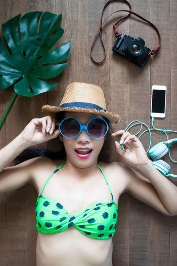 High Angle View Portrait Of Woman Wearing Sunglasses And Hat While Lying On Hardwood Floor