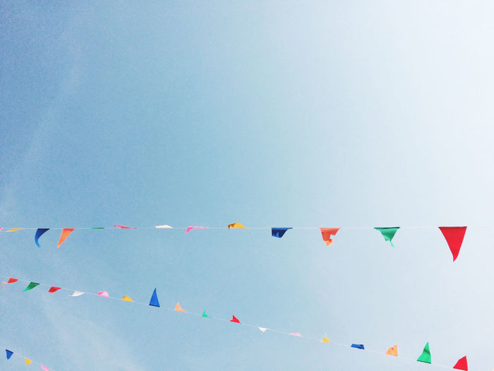 Abundance Blue Celebration Clear Sky Colorful Copy Space Flag Hanging Identity In A Row Large Group Of Objects Low Angle View Multi Colored National Flag No People Order Patriotism Red Sky Variation