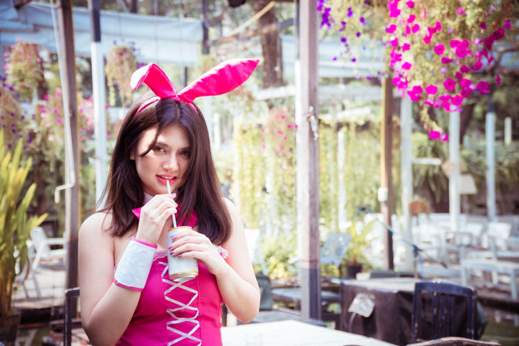 Portrait of a beautiful woman in rabbit costume with drink