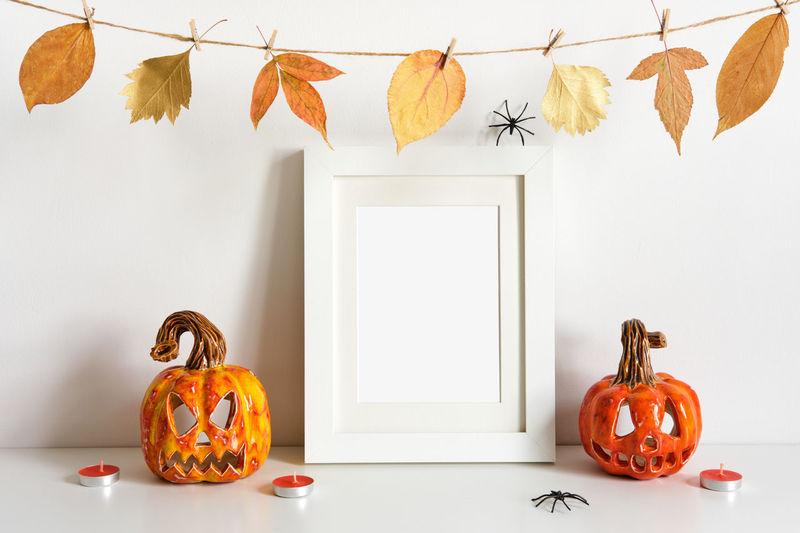 Various pumpkins against orange wall