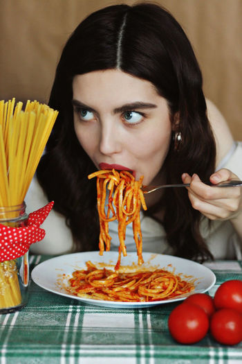 Woman eating pasta in restaurant