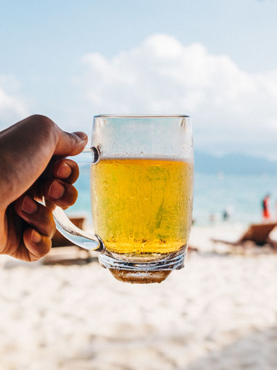 Close-up of hand holding beer glass on beach against sky