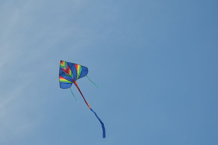 Low Angle View Copy Space Motion Flying Blue Mid-air Single Object Kite - Toy Wind Multi Colored Clear Sky Day Fun Outdoors No People Green Color Vibrant Color Independence