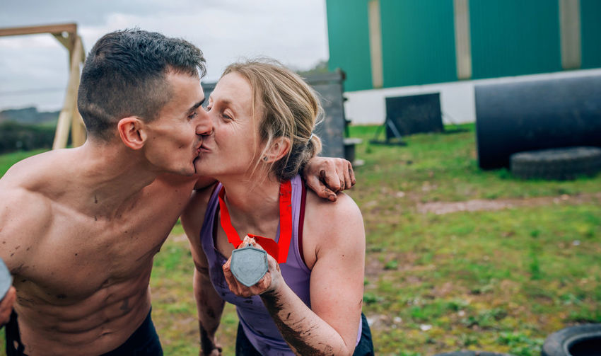 Couple of athletes kissing and showing their medals after a race Obstacle Race Obstacle Course Ocr Collaboration Cooperation Runner Sport Horizontal Extreme Sports Competition Training Workout Strong Boot Camp Effort Power Determination Showing Medal Smiling Champion Couple Kissing Woman Man
