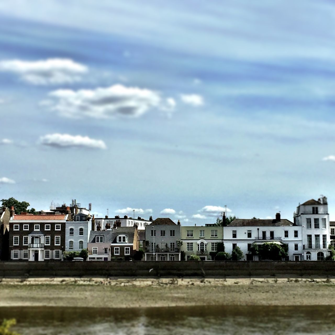 Houses By Thames River Against Sky