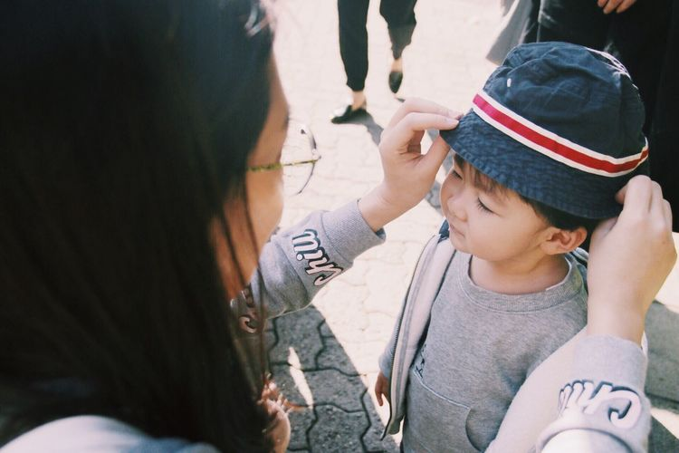 Two People Togetherness Bonding Leisure Activity Childhood Sunlight Outdoors Happiness Family People Real People Boy Child Hat Mother Son Love This Is Family