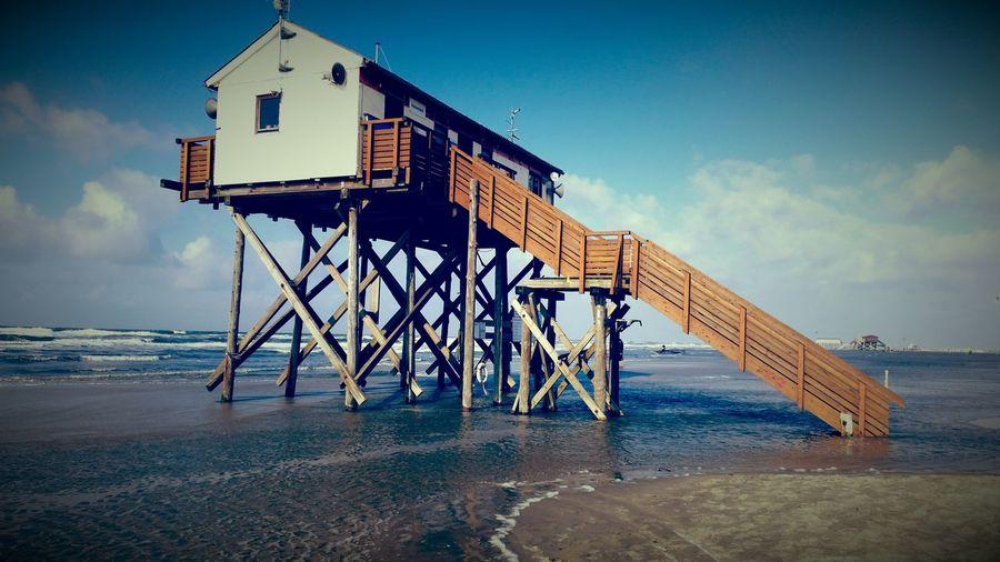 Stilt House At Beach Against Sky