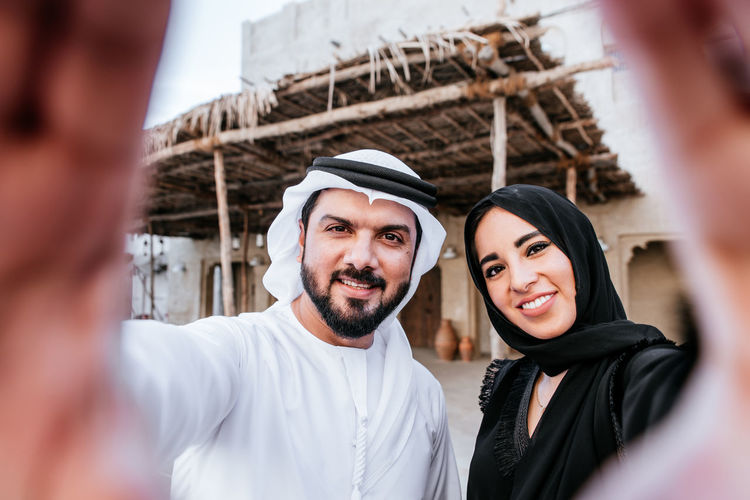 Portrait of smiling couple making hand sign