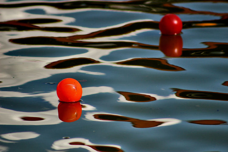 High angle view of orange buoys floating in river