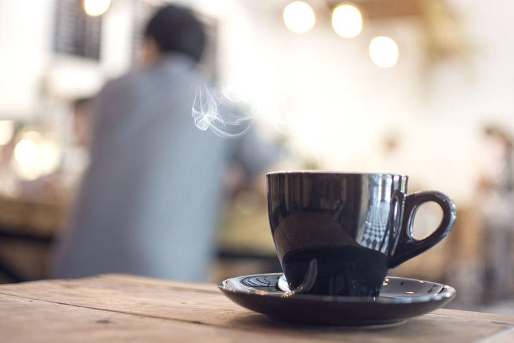 Close up cup of steam hot coffee on the wooden table with blurred man sitting in the cafe Cafeine Hot Latte Mocha Sitting Steam Aroma Bokeh Cafe Cafe Time Cappuccino Coffee Coffee Shop Cup Drink Mug One Person Table Tea Cup Wooden