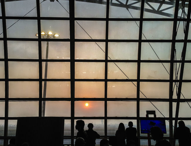 Tourists waiting for morning flight at the airport gate and they looking through the window glass to see the beautiful of sunrise. Sunshine in the morning keep back light and silhouettes of travelers Back Light Boarding Passenger Silhouette Sunrise - Dawn Sunrise Silhouette Tourist Waiting Airport Gate Architecture Back Lighting Built Structure Glass Wall Illuminated Indoors  Lifestyles Men Morning Flight People Real People Silhouette Sunrise Sunshine Tourist Destination Traveller Window Glass