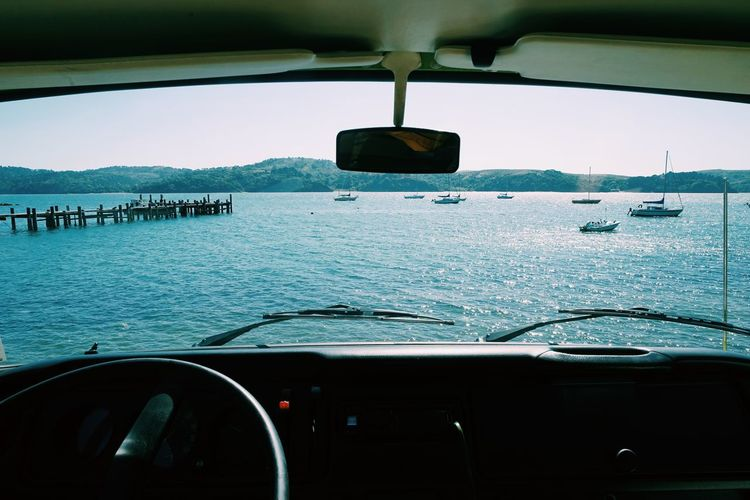 View of sea seen through car windshield