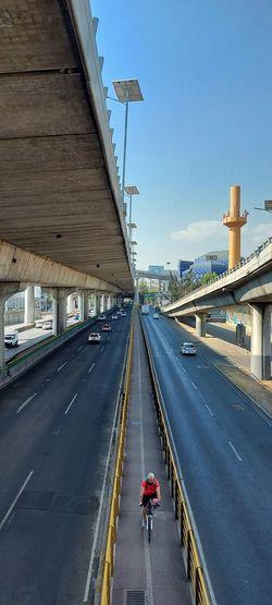 Man riding bridge on road in city against sky