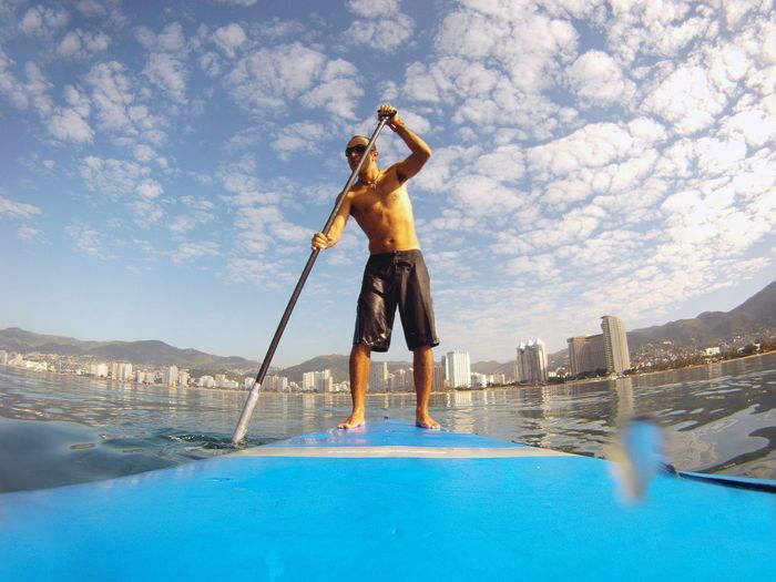 Full length of shirtless man paddleboarding in sea
