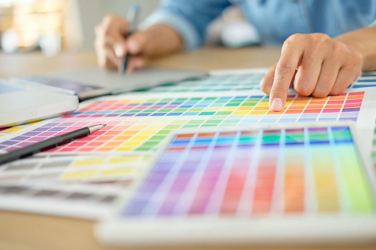Midsection of male graphic designer with color swatch at desk