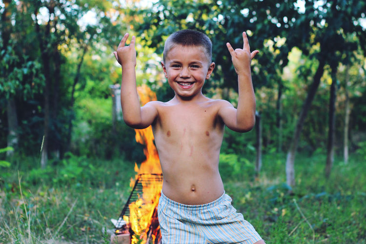 Portrait of happy boy gesturing while standing against bonfire