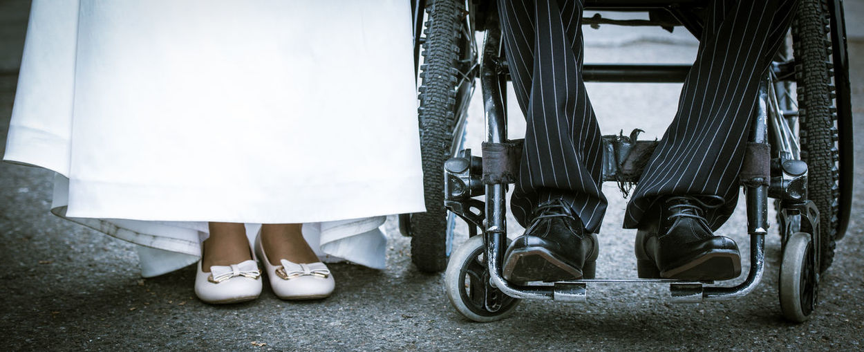 Low section of bride standing by bridegroom on wheelchair