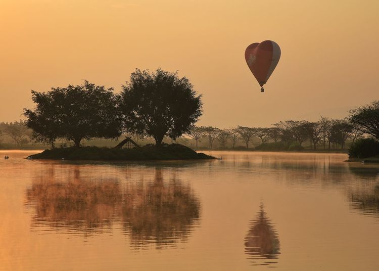 Hot air balloon flying over lake against sky during sunset