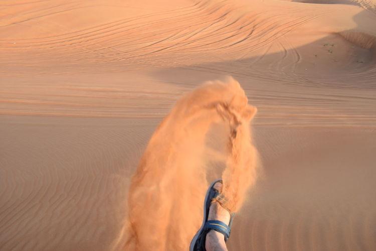 Low section of man kicking sand at desert