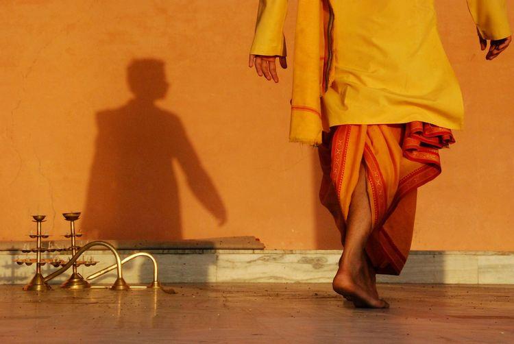 Low section of priest walking on floor against orange wall