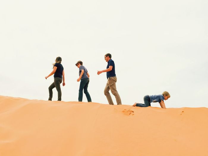 Low angle view of family on sand dune at desert against clear sky