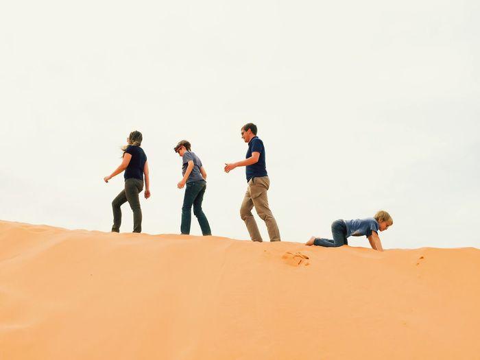 Friends standing on sand dune in desert against clear sky